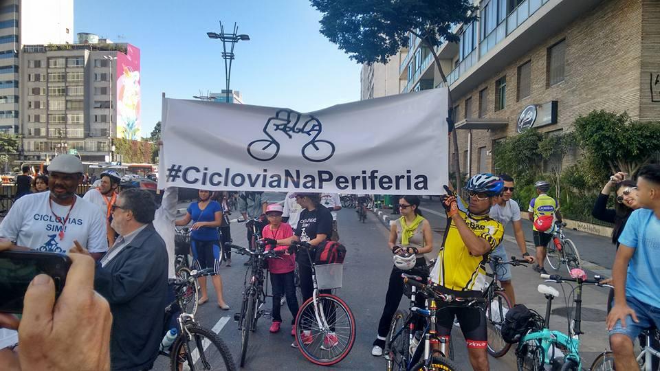 """À esquerda, Roberson Miguel, o cicloativista @biosbug, porta orgulhoso a camisa """"Ciclovias sim"""" e acompanha a faixa """"#CicloviaNaPeriferia"""""""