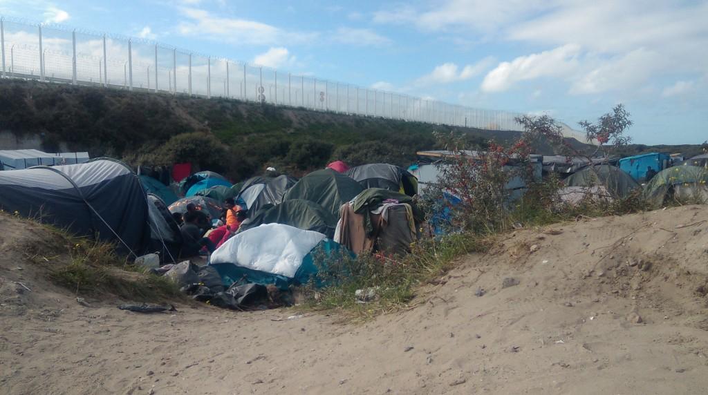 Refugiados instalados na entrada do campo New Jungle. Acima, a longa cerca com arame farpado que separa a New Jungle do porto de balsas de Calais, com destino a Londres. (fotos Marcia Bechara)
