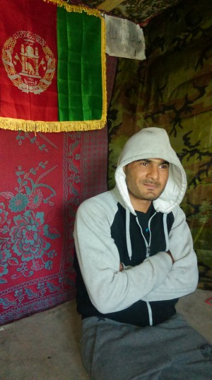 O afegão Ibrahim (ou Rachid) dentro da tenda-restaurante Chicken & Soup, com a bandeira afegã ao fundo